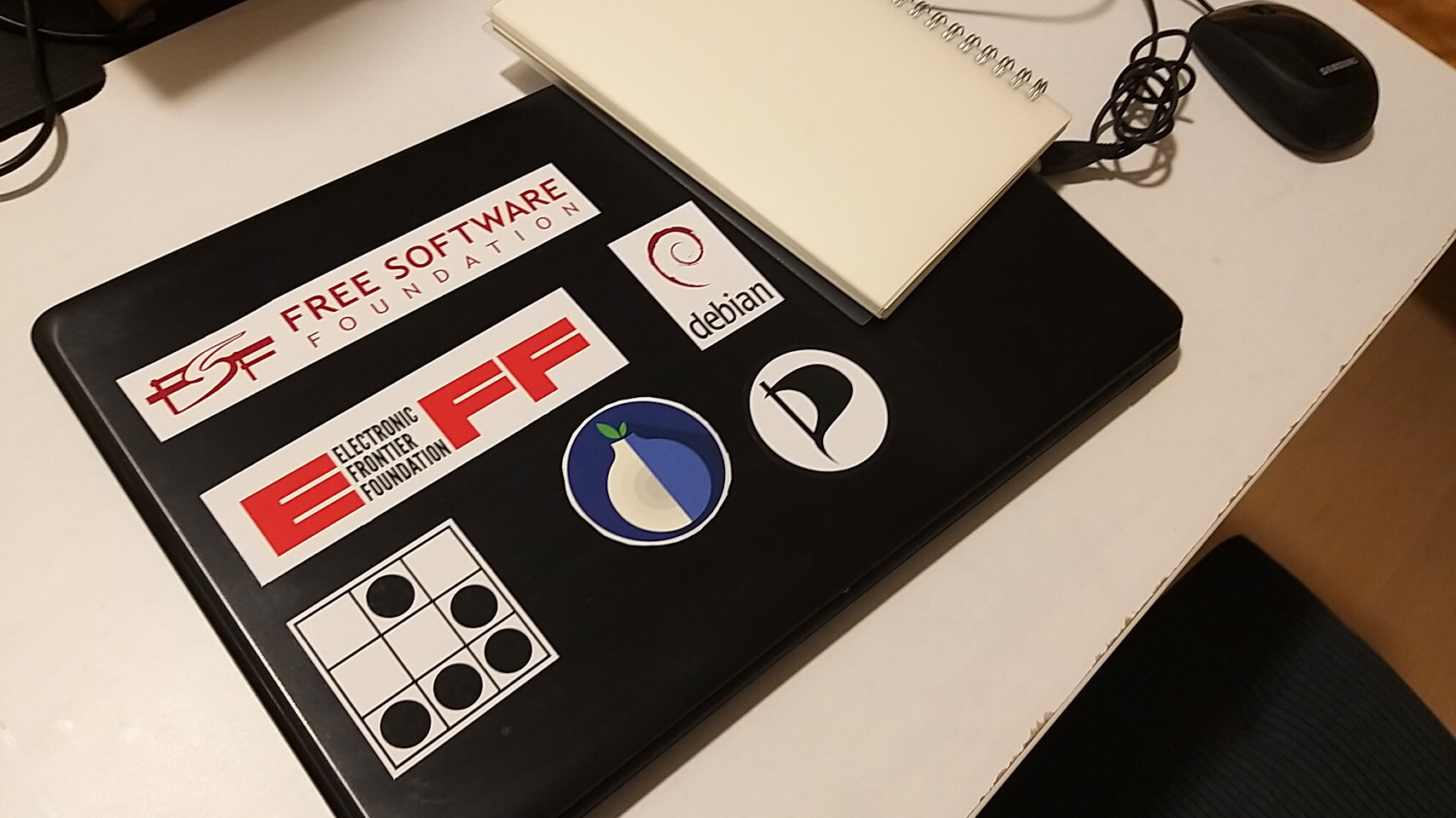 A laptop with lots of Free Software projects and organizations' stickers
