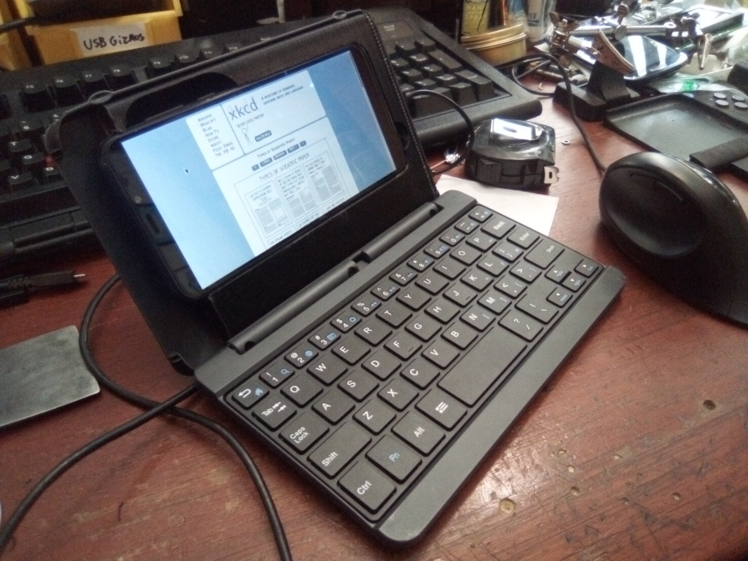 3d printed phone holder in a mildly hacked laptop style tablet keyboard case holding a pinephone from left
