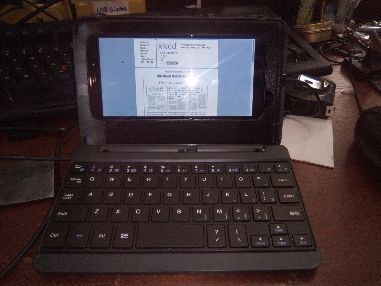 3d printed phone holder in a mildly hacked laptop style tablet keyboard case holding a pinephone from straight ahead